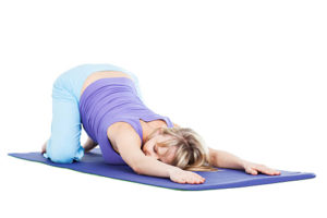 Pregnant woman doing relaxing exercising on fitness mat isolated